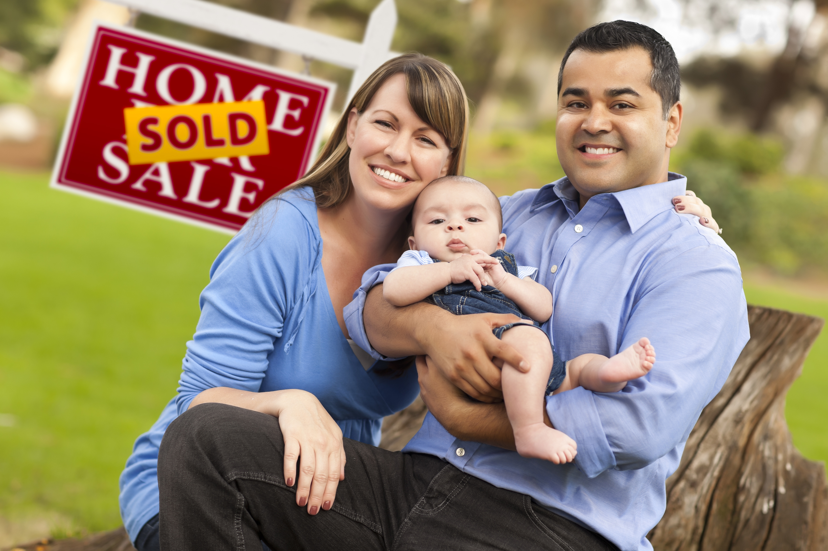 Happy Mixed Race Couple with Baby in Front of Sold Real Estate S